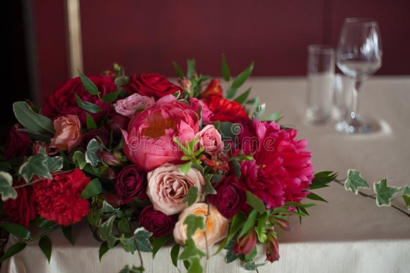 背景钮扣眼上插的花看板卡装饰装饰邀请婚姻白色的珍珠玫瑰 红色花在餐馆,桌设置 免版税库存照片