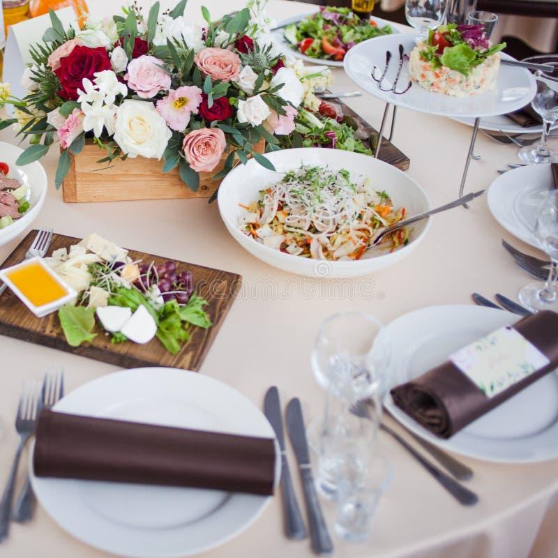 背景钮扣眼上插的花看板卡装饰装饰邀请婚姻白色的珍珠玫瑰 花在餐馆,在桌上的食物 免版税库存图片