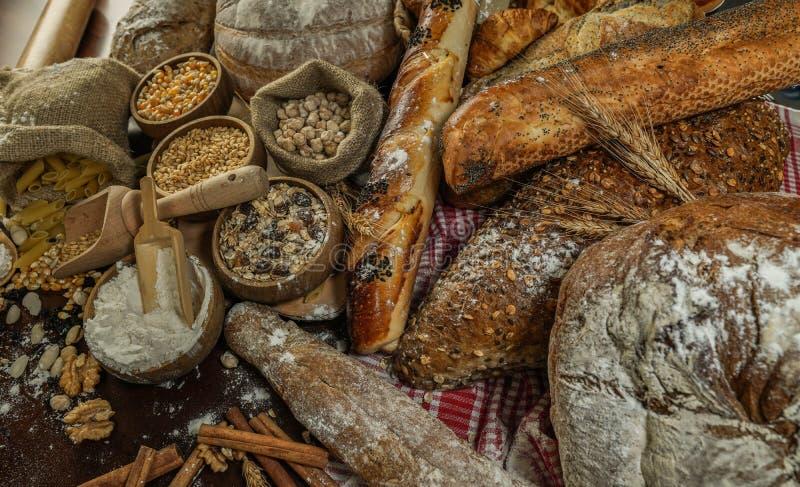 背景面包框架全景 在土气黑暗的木头的牛皮纸构成和白色整个五谷大面包包裹的布朗与麦子耳朵scatte 图库摄影