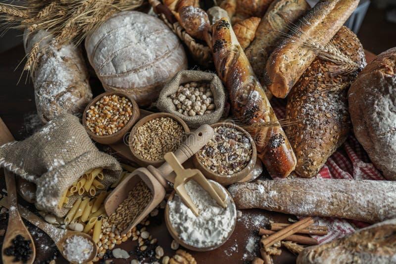 背景面包框架全景 在土气黑暗的木头的牛皮纸构成和白色整个五谷大面包包裹的布朗与麦子耳朵scatte 免版税图库摄影