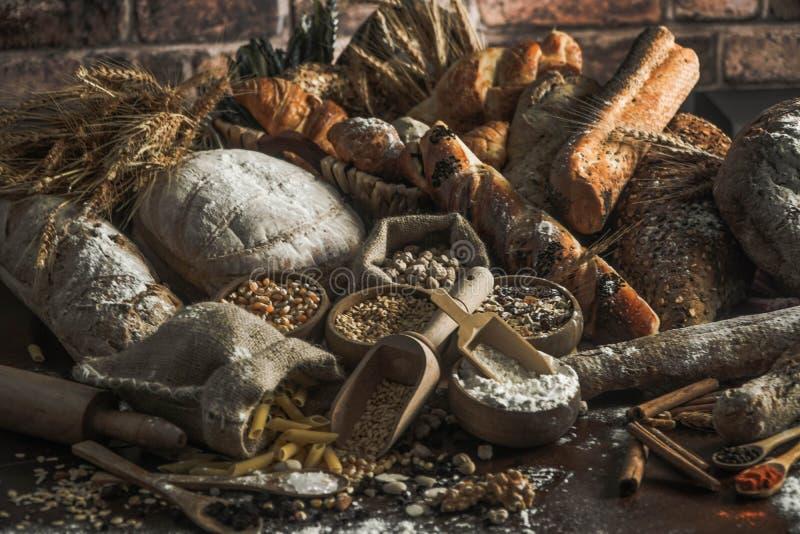 背景面包框架全景 在土气黑暗的木头的牛皮纸构成和白色整个五谷大面包包裹的布朗与麦子耳朵scatte 库存图片