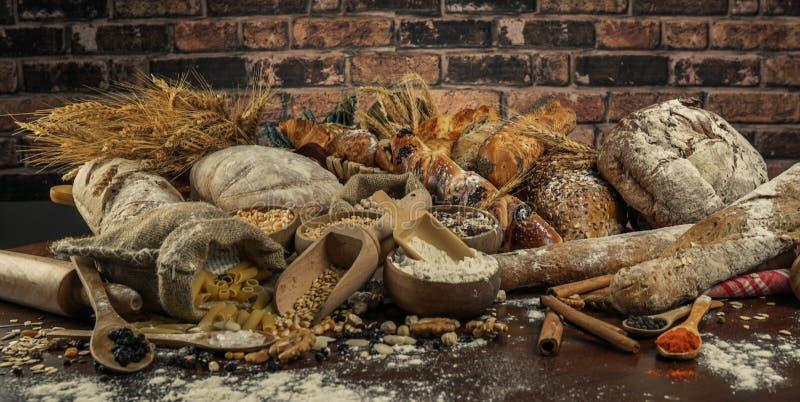 背景面包框架全景 在土气黑暗的木头的牛皮纸构成和白色整个五谷大面包包裹的布朗与麦子耳朵scatte 免版税库存照片