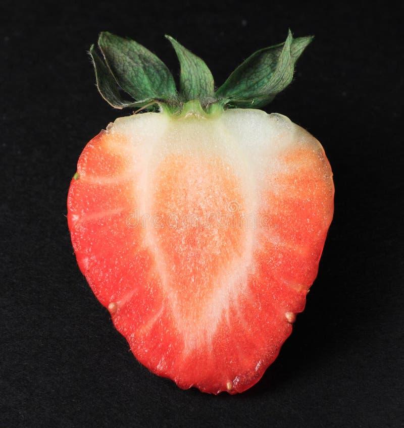 背景黑色被对分的红色草莓 库存图片