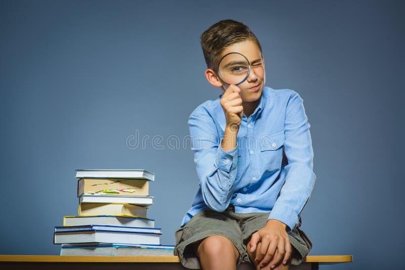 背景黑名册概念copyspace学校 怀疑坐书桌和调查放大镜的男孩 免版税库存图片
