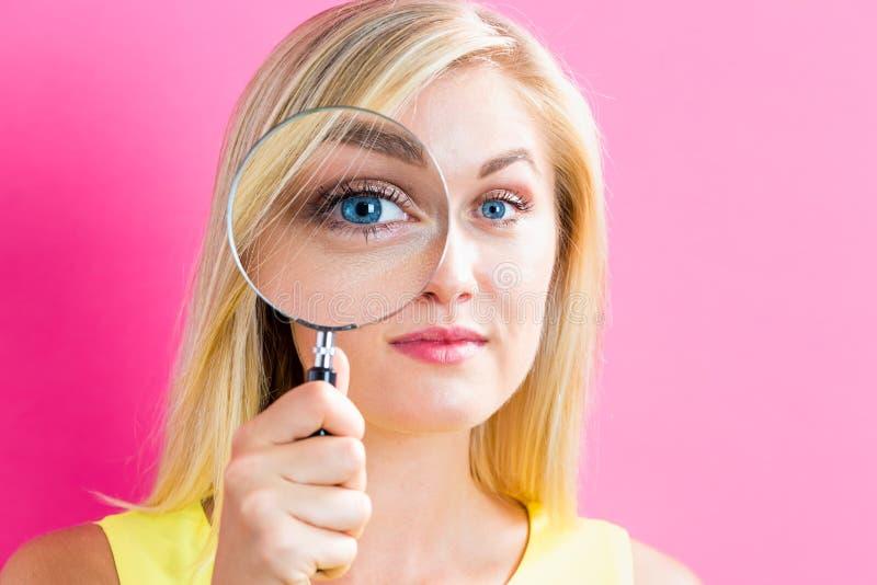 背景玻璃查出看起来扩大化的白人妇女年轻人 免版税图库摄影