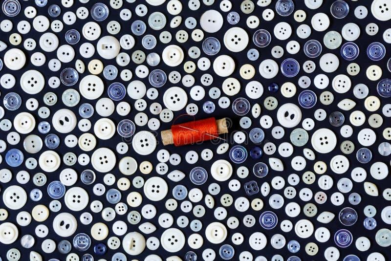 背景-红色螺纹一个黑暗的表面和卷轴上的轻的按钮与针的 库存图片
