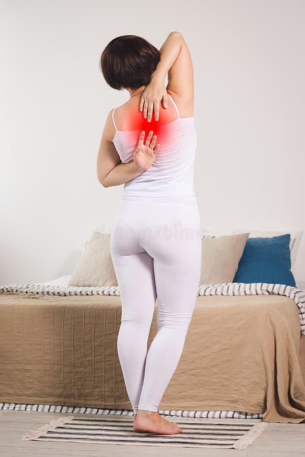 背部疼痛,从腰疼的妇女痛苦在家 免版税库存照片