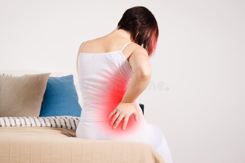 背部疼痛,肾脏炎症,在家遭受腰疼的妇女 免版税库存图片