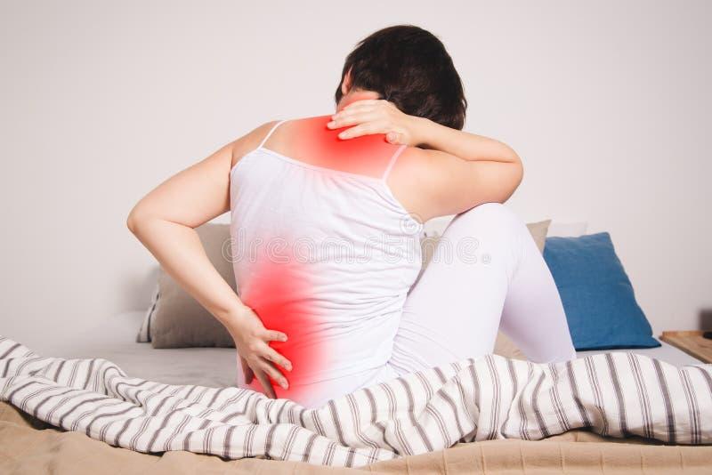 背部疼痛,肾脏炎症,在家遭受腰疼的妇女 图库摄影