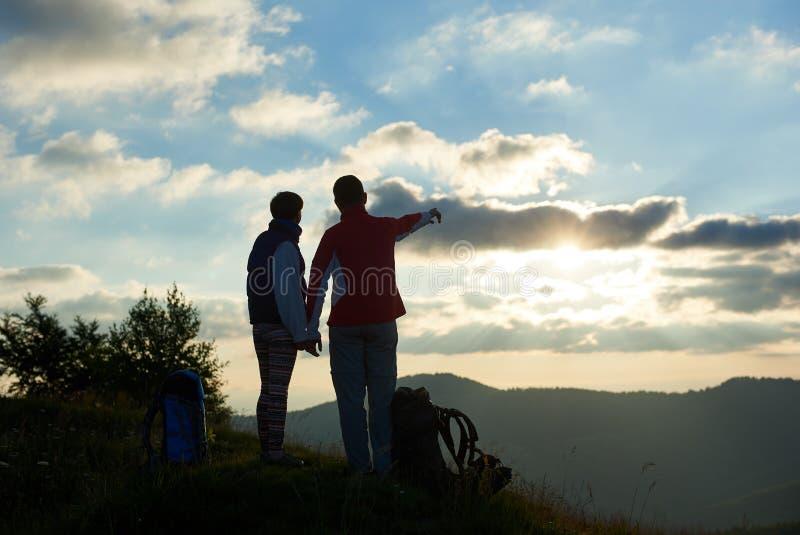 背面图两游人站立在山顶部反对多云天空在日落 免版税图库摄影