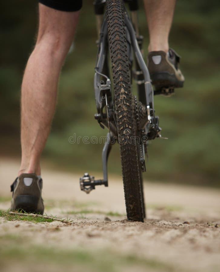 背面图低角度在登山车的人腿 免版税库存照片