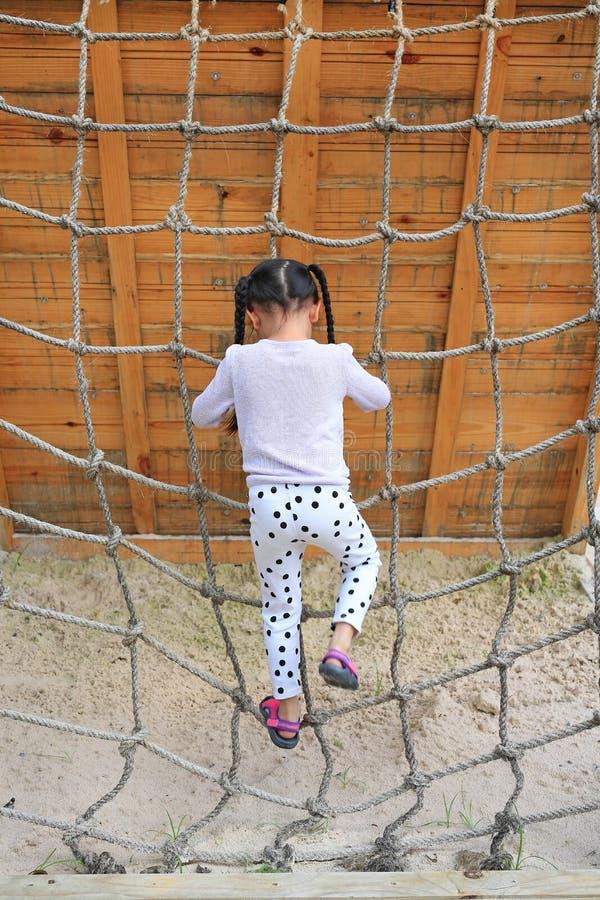 背面图使用在上升的绳索网的操场的小孩女孩 图库摄影