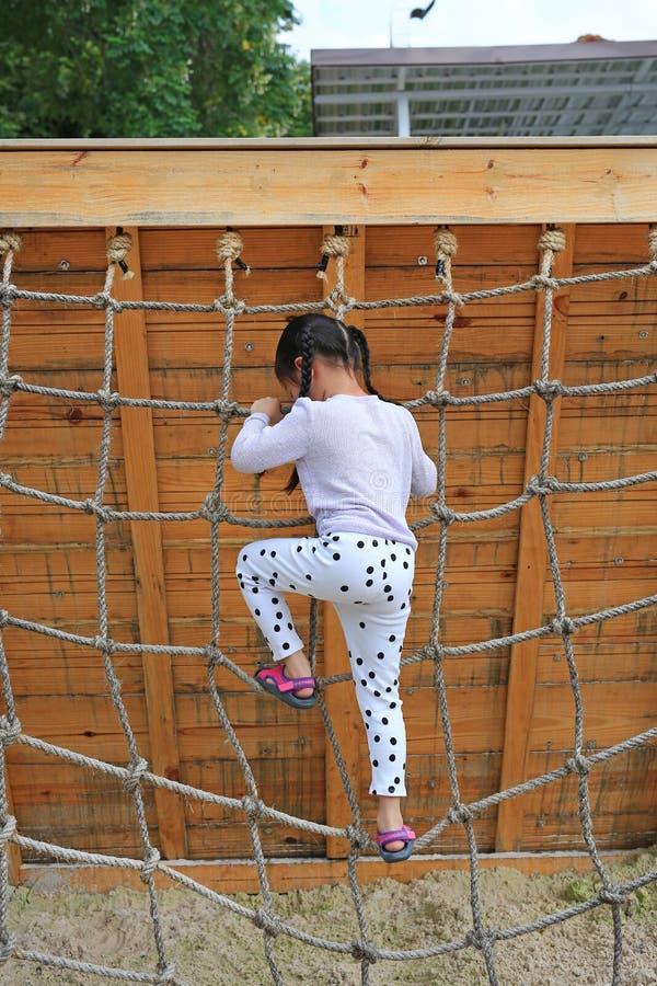 背面图使用在上升的绳索网的操场的小孩女孩 库存图片