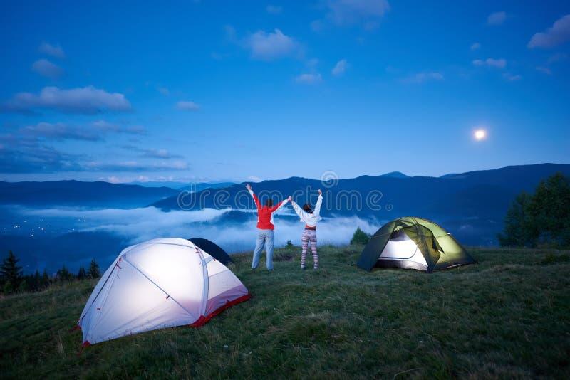 背面图好朋友近野营在握手的山向上培养了他们 免版税库存图片