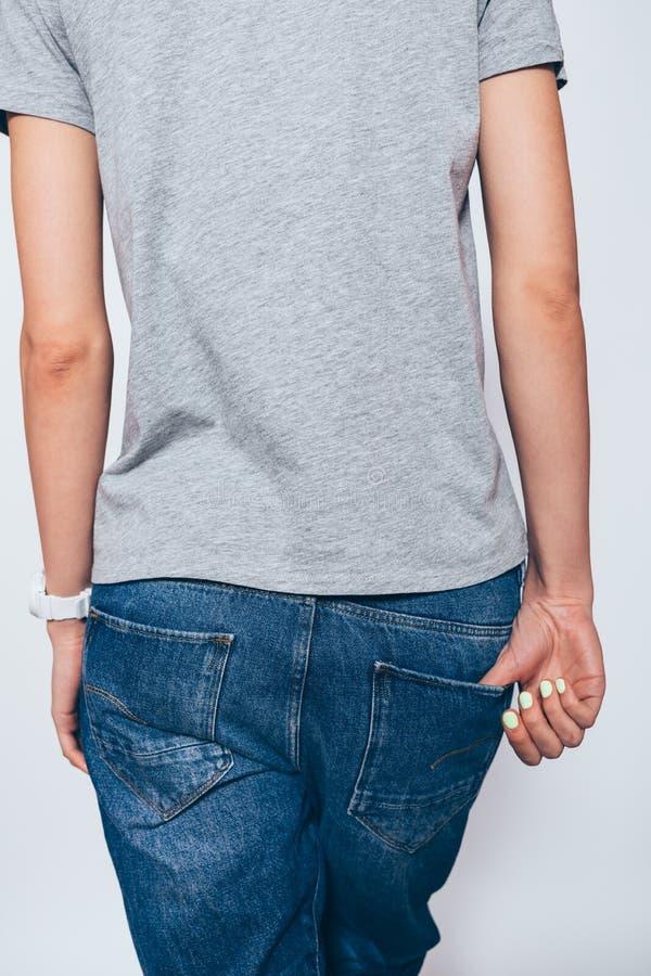 背面图时髦的年轻女人佩带的蓝色牛仔裤 免版税库存图片