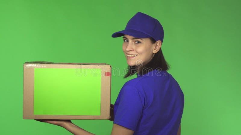背面图有纸板箱的交付妇女微笑在她的肩膀的射击了  库存照片