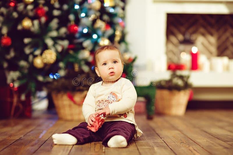 胖的矮小的逗人喜爱的女婴1在地板上的岁开会 免版税图库摄影