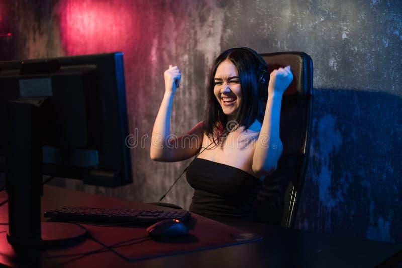 胜利和纯净的情感愉快的快乐的逗人喜爱的性感的游戏玩家女孩手势  在家打单独电子游戏坐a 库存图片
