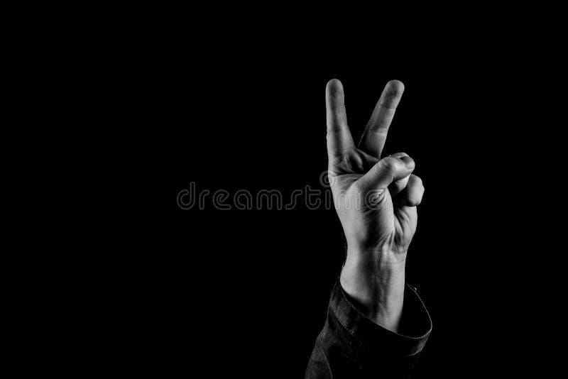 胜利姿态,佩带长的袖子的人显示V形标志,黑白拷贝空间 免版税库存照片