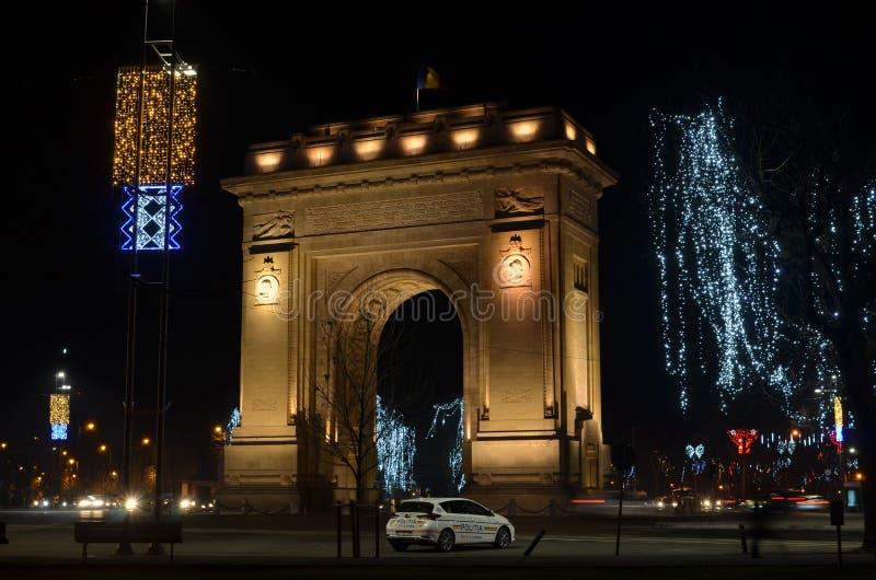 胜利布加勒斯特曲拱在夜和圣诞灯的 免版税库存图片