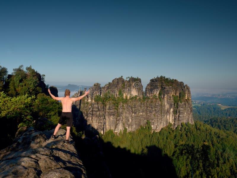 胜利黑裤子姿态的登山人  岩石的身体赤裸人 免版税库存图片