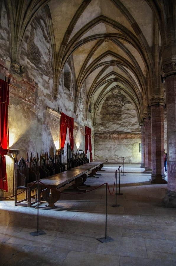 胡内多阿拉,罗马尼亚- 2019年5月3日:在Corvin城堡里面 葡萄酒王位与老木位子和长的木桌的室内部, 图库摄影