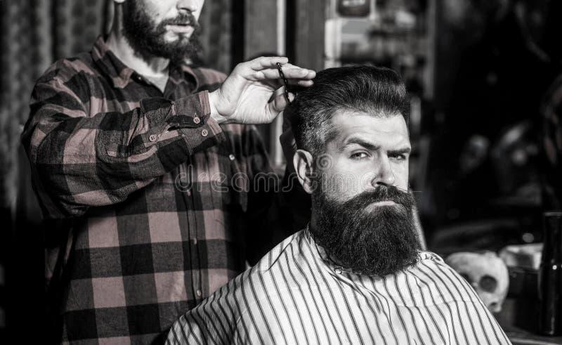 胡子人在理发店 发式专家服务客户在理发店,有胡子 美发师,有胡子的人 r 免版税库存照片
