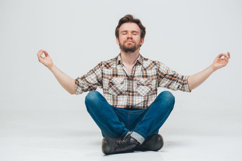 年轻胡子人坐地板思考 免版税库存图片