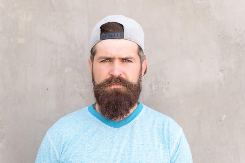 胡子和髭修饰 行家生活方式 有胡子穿戴时髦的棒球帽的凉快的行家 残酷英俊 免版税库存照片