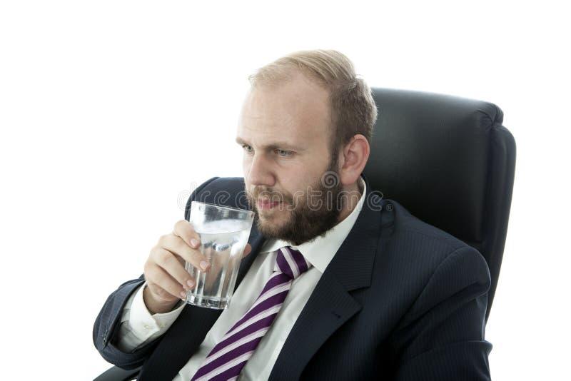 胡子商人饮料玻璃水,当工作时 免版税库存照片