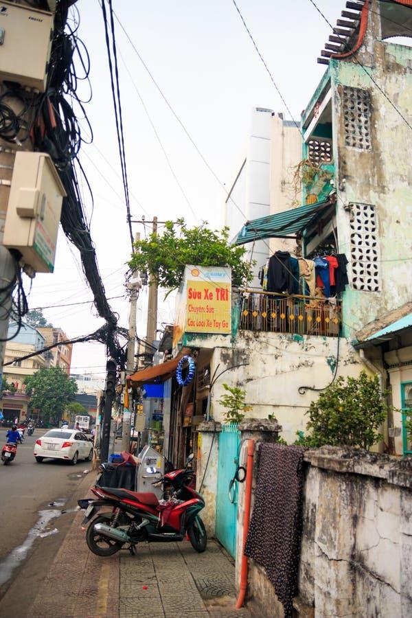 胡志明市,越南- 2018年12月:在老大厦中的有摩托车的牌,路,汽车和被缠结的导线 免版税库存图片
