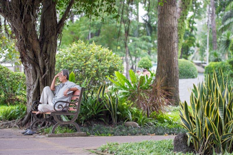 胡志明市,越南- 2018年9月1日:坐在考虑某事的公园的角落的一个未定义人 免版税库存照片