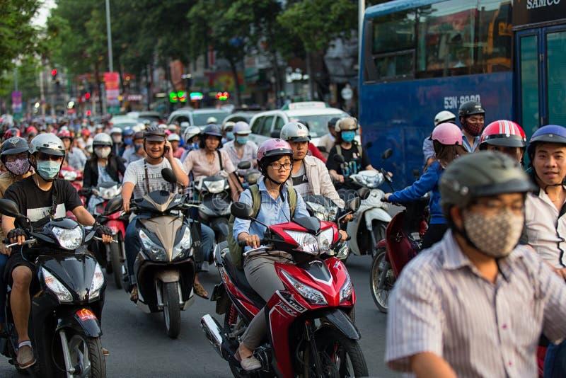 胡志明市,越南- 2015年4月19日:城市交通打鸣的场面在高峰时间,人人群头戴盔甲 免版税库存照片