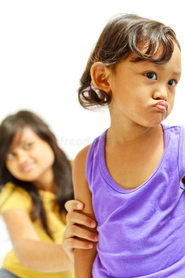 胡思乱想的子项说服青少年的姐妹 免版税图库摄影