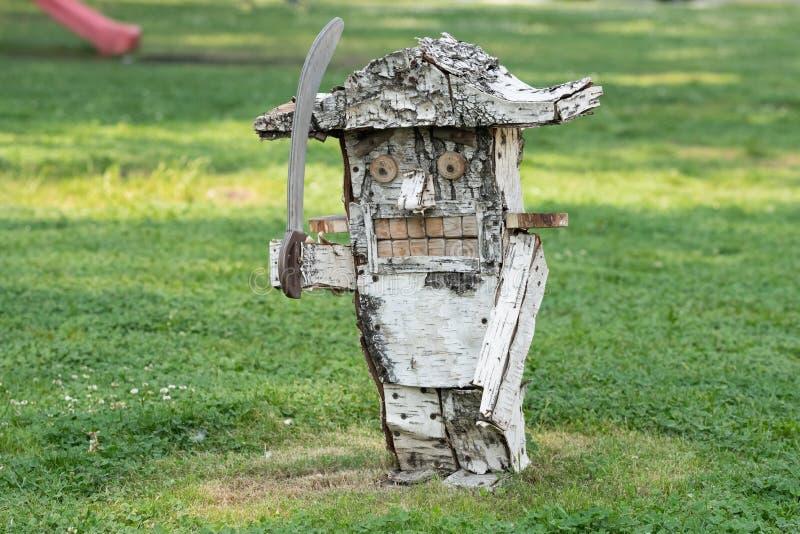 胡桃钳的一个木雕塑手工制造从在草背景的桦树  免版税图库摄影
