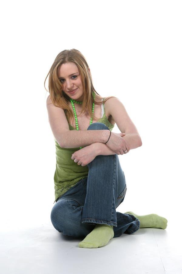 胳膊克服俏丽的坐的妇女年轻人 图库摄影