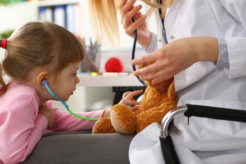 胳膊的女孩举行戏弄使用与玩具熊的听诊器 免版税库存图片