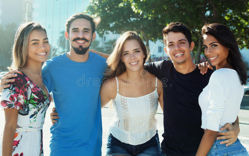 胳膊的笑的白种人和拉丁和西班牙人民 免版税库存图片