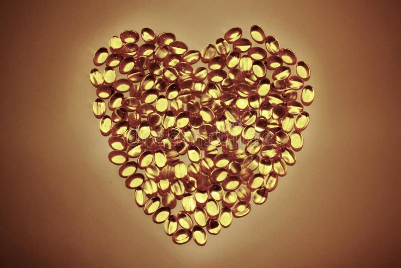 胶凝体药片说谎以在白色背景的心脏的形式,黄色胶囊Ω 3 库存图片