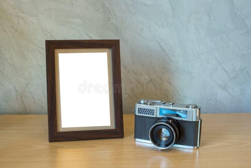 胶卷相机和相框在桌上 免版税库存照片