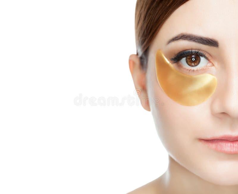 胶原在眼皮的皮肤的金补丁,在面孔 免版税库存照片