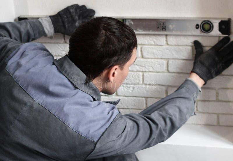 胶合在墙壁上的专业工作者一个瓦片 库存照片