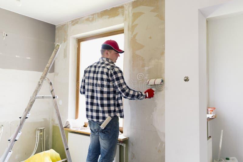 胶合在家贴墙纸 年轻人,工作者投入墙纸在墙壁 家庭整修概念 库存照片