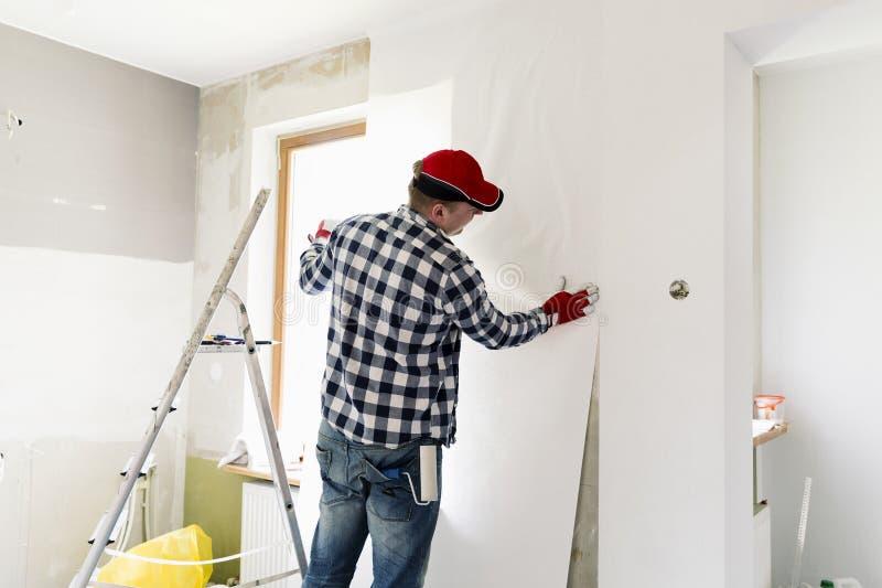 胶合在家贴墙纸 年轻人,工作者投入墙纸在墙壁 家庭整修概念 库存图片