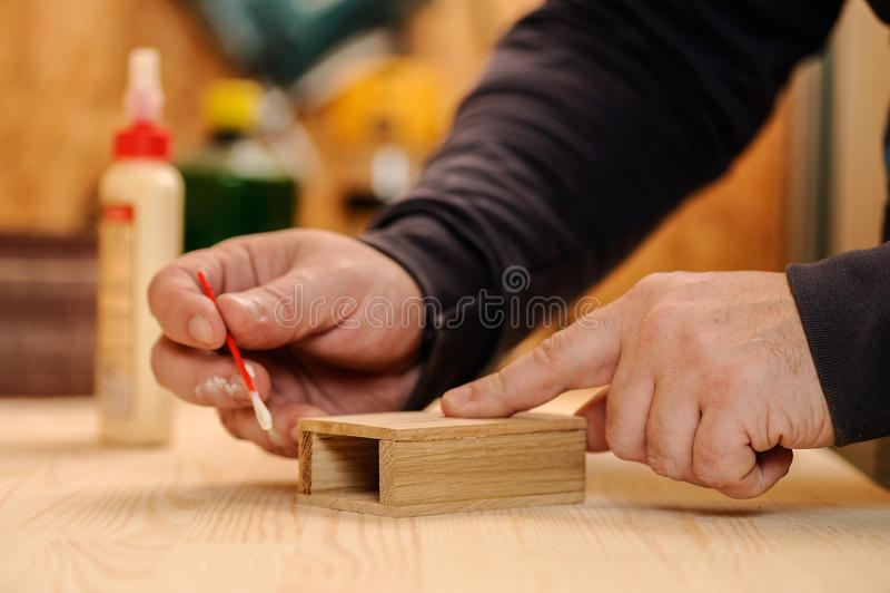 胶合木头的木匠手 库存图片