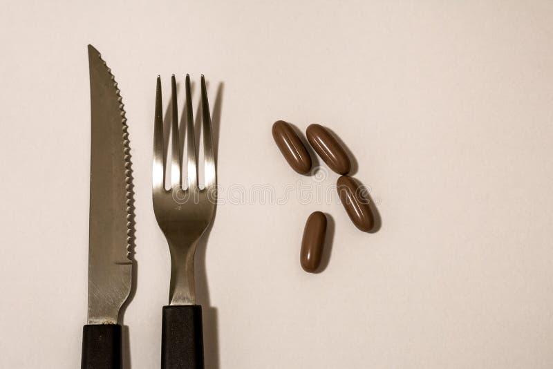 胶囊、药片、叉子和刀子 库存图片