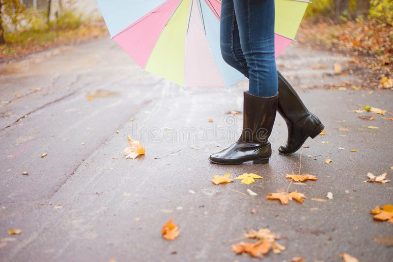 胶靴的妇女走与伞的在一多雨秋天天 库存照片