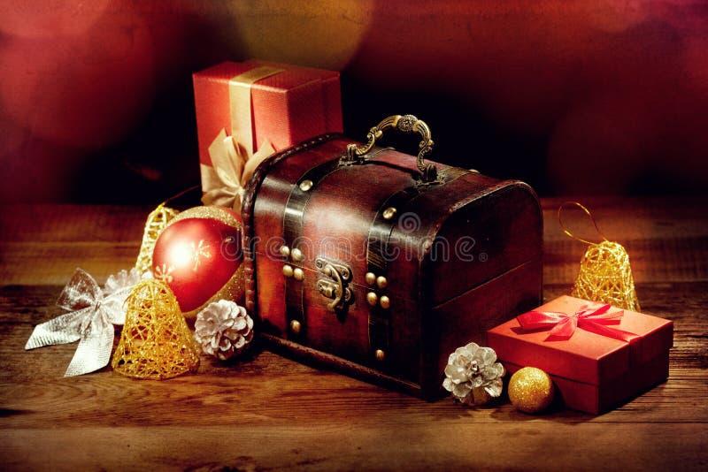 胸口、礼物和其他圣诞节装饰在老木桌上 库存图片