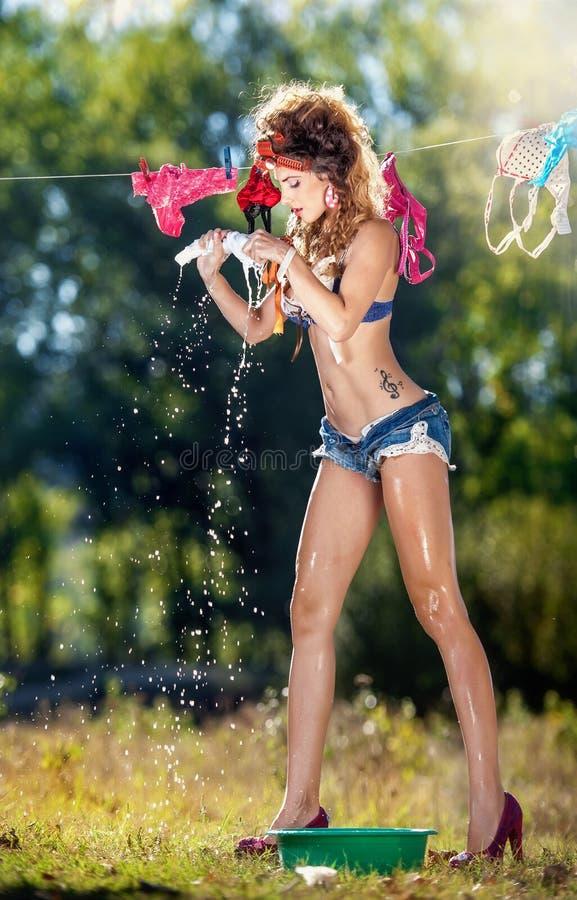 胸罩和牛仔布的性感的深色的妇女在太阳短缺投入衣裳烘干 有室外长的腿的肉欲的年轻女性 库存图片