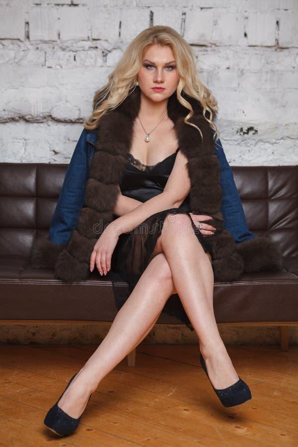 胸罩的年轻女人坐沙发 库存照片